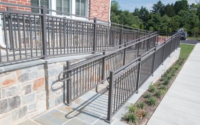 Gray aluminum railings up a handicap accessible ramp