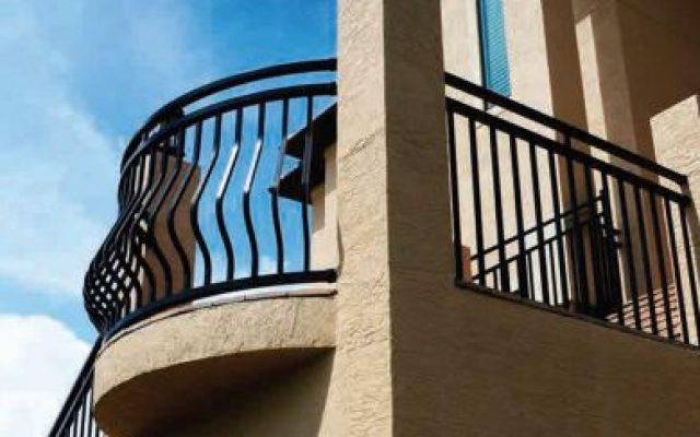 Black aluminum railing around a veranda of a stucco house