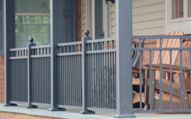 Gray aluminum porch railing around wooden furniture